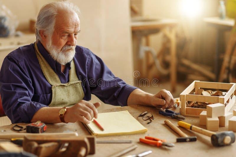 Старый опытный плотник сидя на грязной таблице на рабочем месте стоковые фото