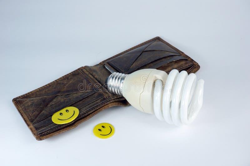 Старый открытый кожаный бумажник с smiley энергосберегающего шарика счастливым смотрит на на белой предпосылке стоковая фотография
