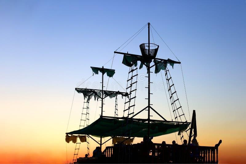 Старый пиратский корабль sailer, с сорванными ветрилами, на заходе солнца стоковая фотография