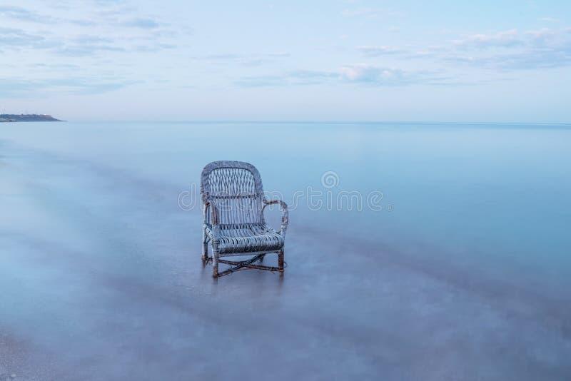 Старый плетеный стул в море Долгая выдержка, минимальный ландшафт стоковое фото rf