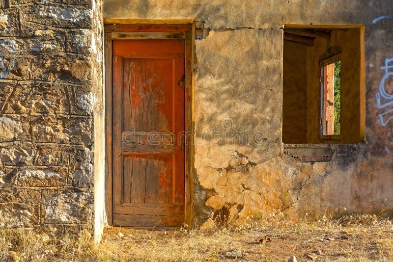 Старый, покинутый дом с красной дверью стоковое изображение
