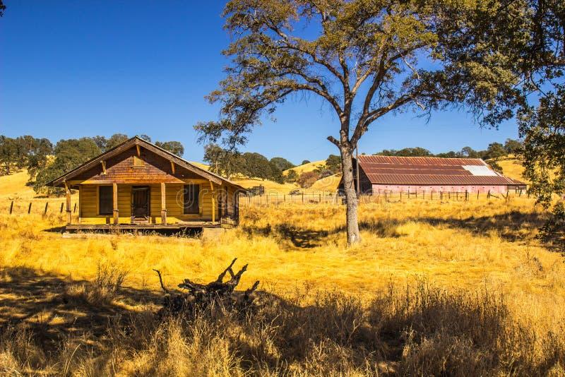 Старый покинутый желтый дом фермы с большим амбаром в Gackground стоковое фото rf