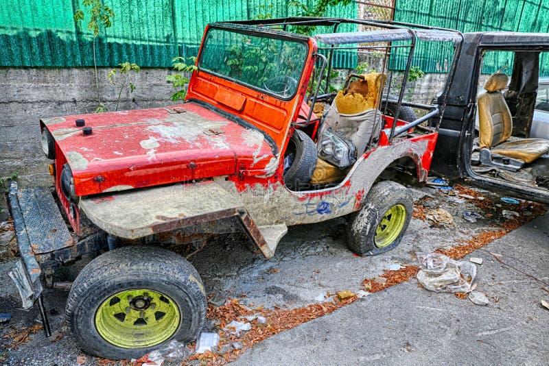 Старый покинутый ржавый красный цвет покрасил виллис на дворе старья редактируемом в hdr стоковое изображение rf