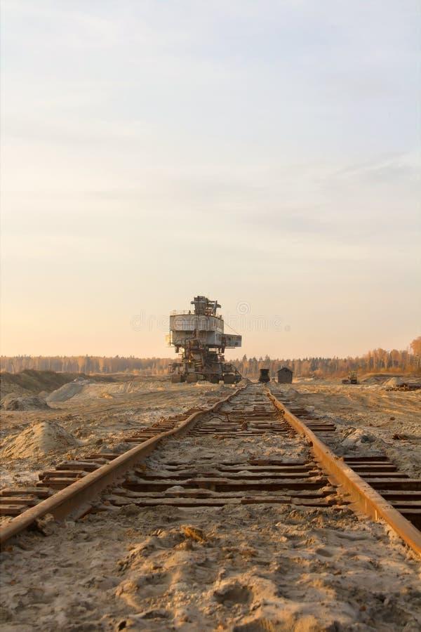 Старый получившийся отказ железнодорожный путь Гигантский штабелеукладчик Экскаватор ковшовой цепи в карьере песка Погрузо-разгру стоковое фото rf