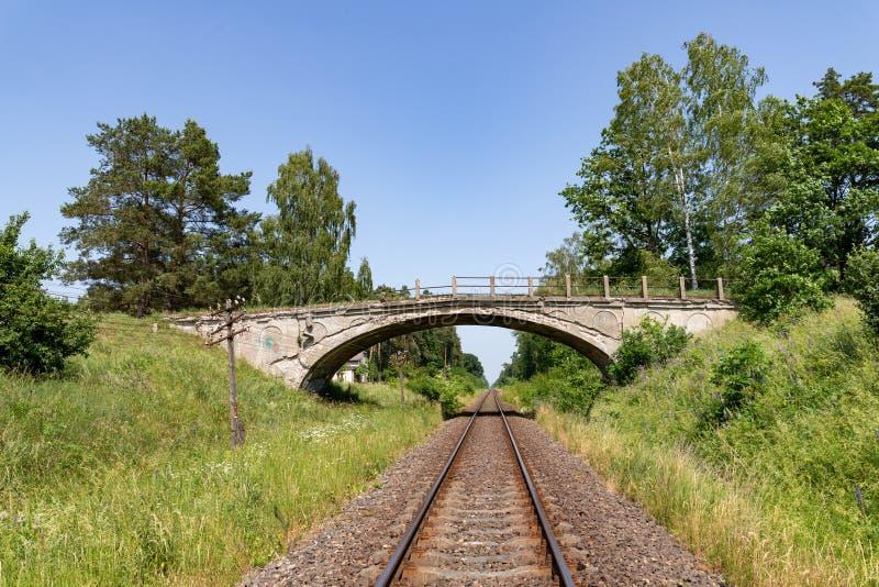 Старый разрушенный конкретный мост над железнодорожным путем Старый железнодорожный путь с линией телеграфа стоковое фото rf