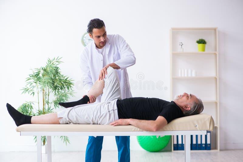Старый раненый человек навещая молодой доктор стоковая фотография rf