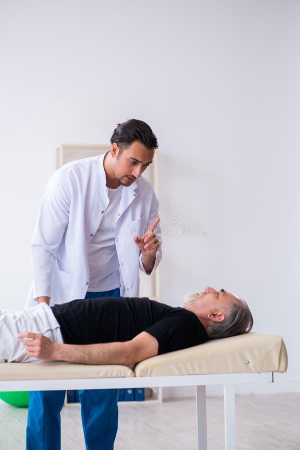 Старый раненый человек навещая молодой доктор стоковое изображение