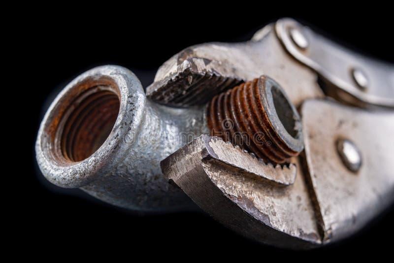 Старый регулируемый гаечный ключ и гидравлический разъем на рабочем столе Гидравлические аксессуары стоковое изображение