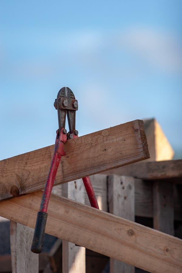 Старый ржавый красный инструмент для нарезания болтов висит на доске конструкции стоковая фотография