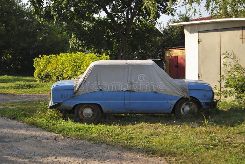 Старый ржавый Совет-сделанный автомобиль ZAZ, покрытый с шатром стоковые фото