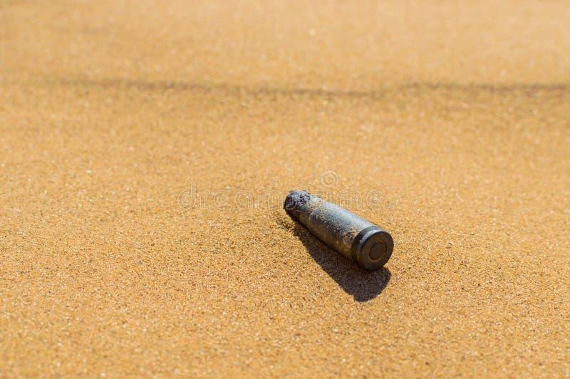 Старый ржавый футляр кассеты пули в конце песка Концепция: вооруженные конфликты на Ближнем Востоке стоковые фото