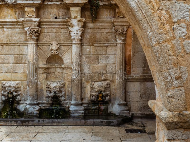 Старый римский каменный фонтан с изумляя деталями сброса стены стоковые фото