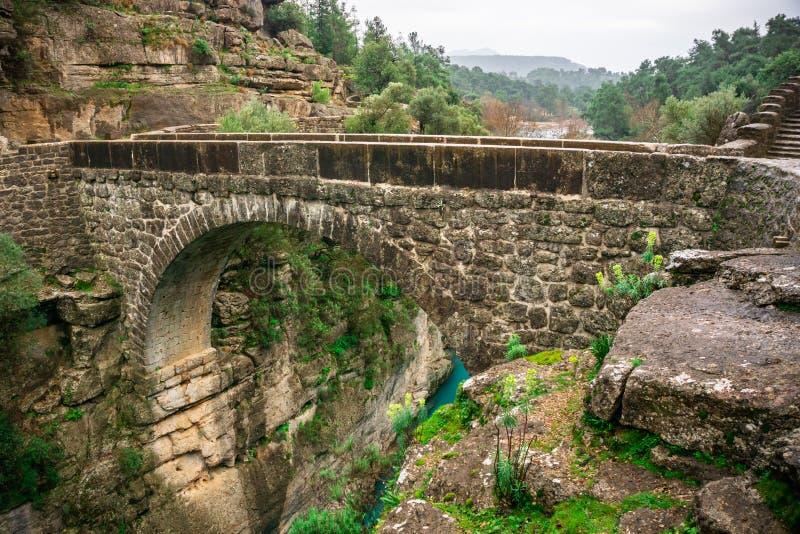 """Старый римский мост как известно как """"мост Bugrum или Oluk """" Ландшафт реки Koprucay от национального парка каньона Koprulu стоковые изображения"""
