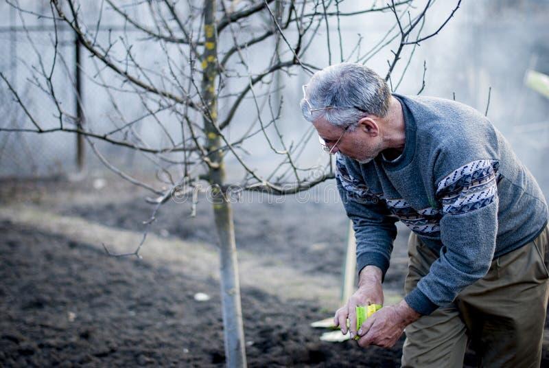Старый румынский человек работая его земля в традиционном пути с пустыми руками стоковое изображение