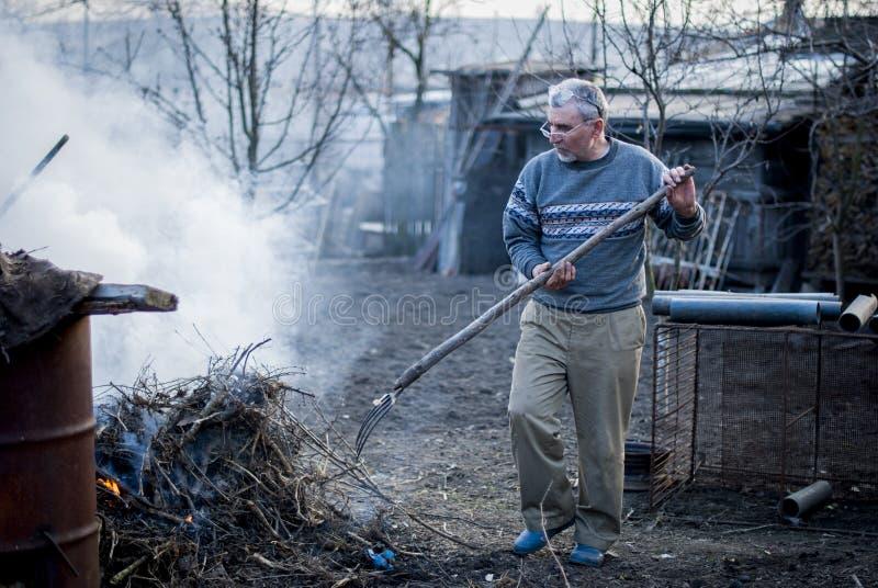 Старый румынский человек работая его земля в традиционном пути с пустыми руками стоковые изображения rf