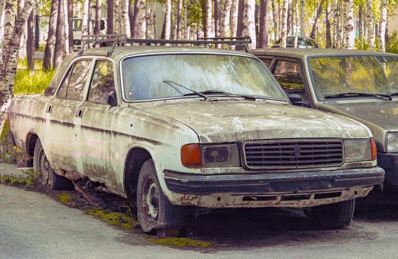 Старый русский автомобиль покрытый с грязью и мхом с плоской катит во двор стоковые изображения
