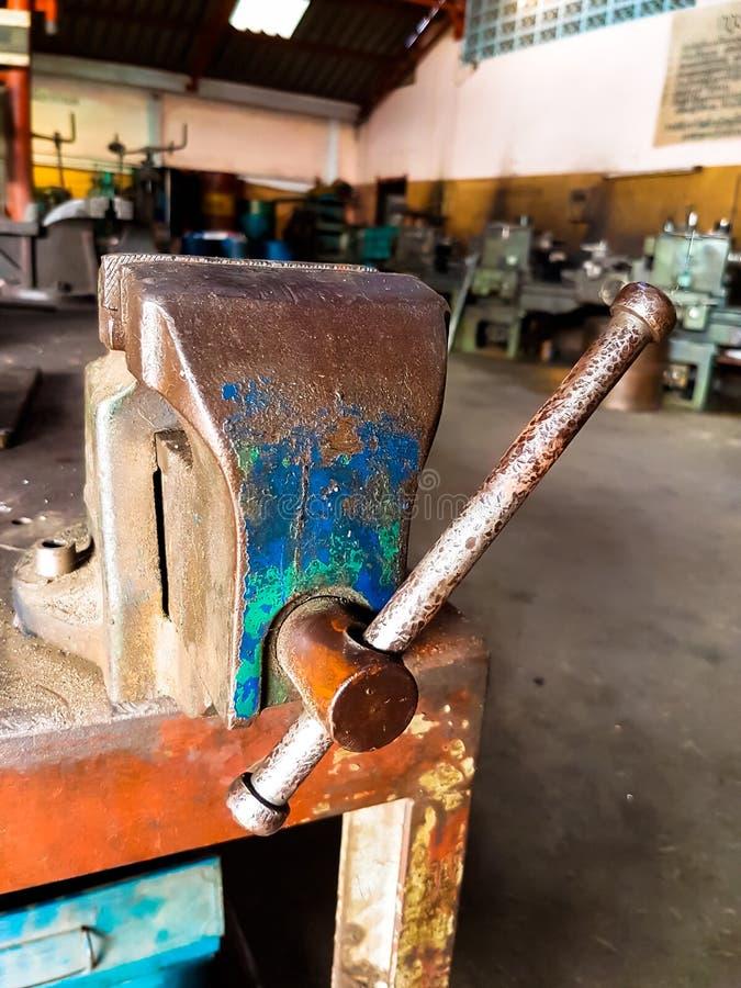 Старый ручной резец тисков стенда с ржавчиной на таблице стоковое фото rf