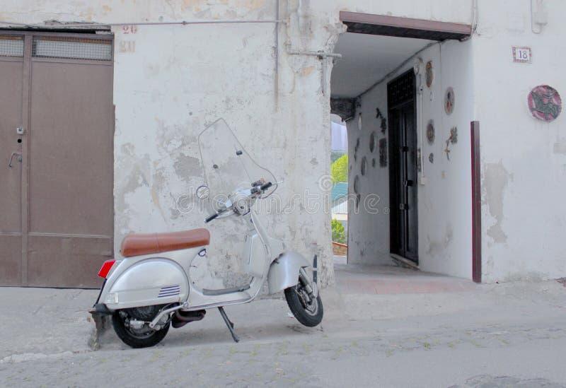 Старый самокат на улице стоковые фото