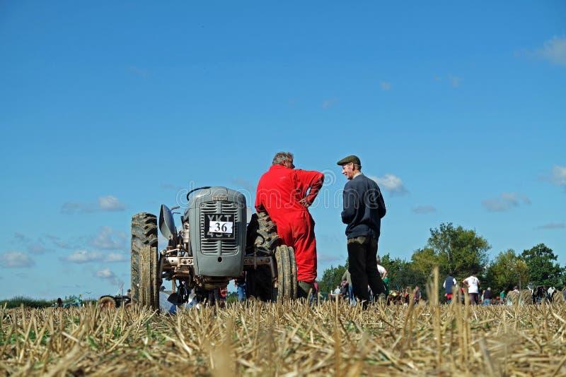 Старый серый трактор Ferguson и красный одетый водитель стоковые изображения