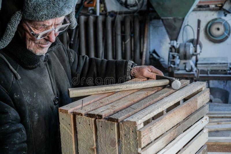 Старый серьезный мастер в серых теплых одеждах и шляпе, в eyeglasses стоковая фотография rf