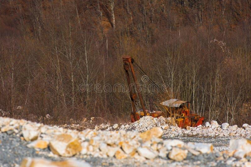 Старый сломанный покинутый ржавый экскаватор в карьере стоковое фото rf