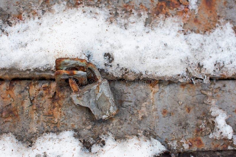 Старый сломанный ржавый padlock в снеге стоковое изображение rf