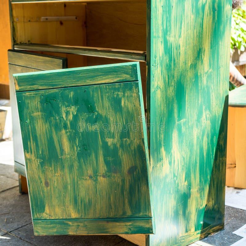 Старый сломанный шкаф, который подготовлен с первым пальто зеленой краски для более дополнительных ремонта и реновации, стоковая фотография