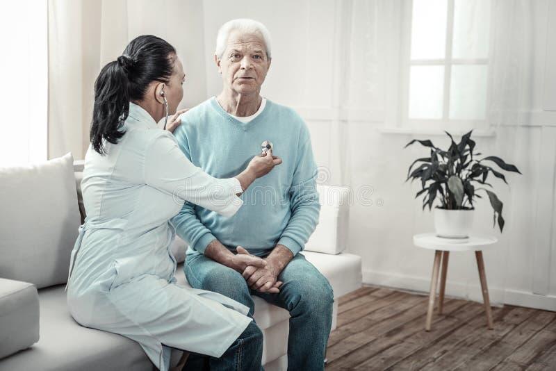 Старый смущающий человек сидя и имея медицинский осмотр стоковое фото