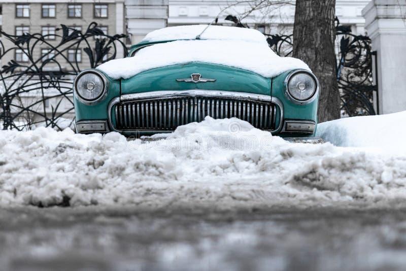 Старый советский автомобиль Волга Автомобиль бирюзы ретро покрытый со снегом GAZ-21 на улице стоковые фотографии rf