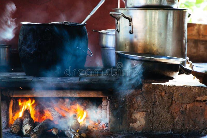 Старый стиль варя с большим баком на открытом огне Варить черного большого бака утюга традиционный на огне журнала деревянном с в стоковые фотографии rf