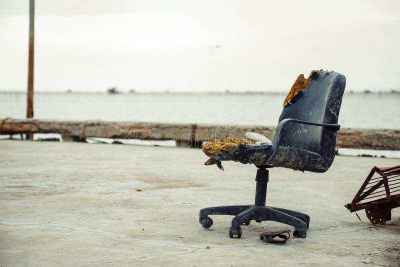 Старый стул офиса внешний около моря и сандалий под стулом стоковое изображение