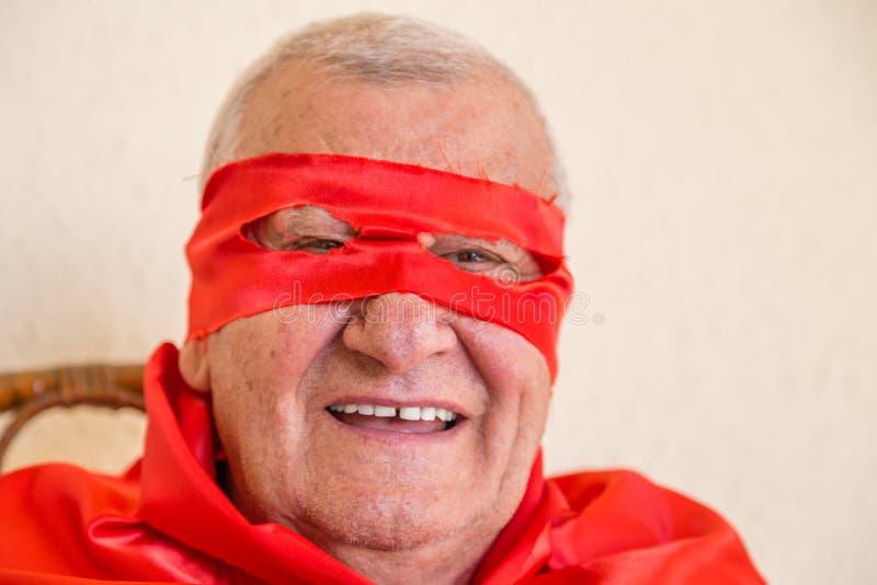 Старый супергерой держа красную розу стоковое фото rf