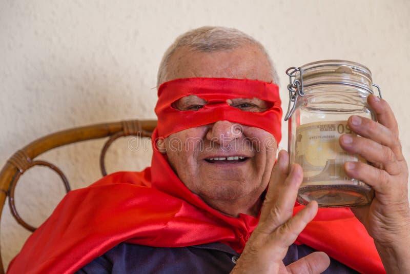 Старый супергерой держа опарник денег стоковая фотография