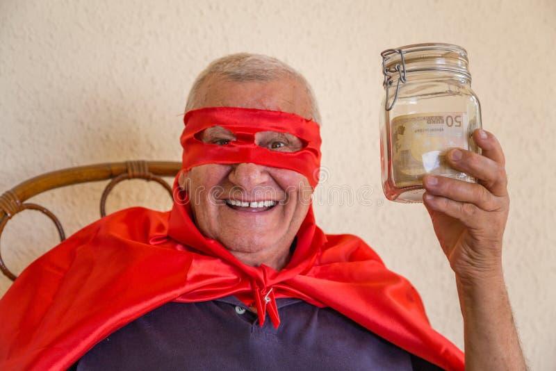 Старый супергерой держа опарник денег стоковые изображения