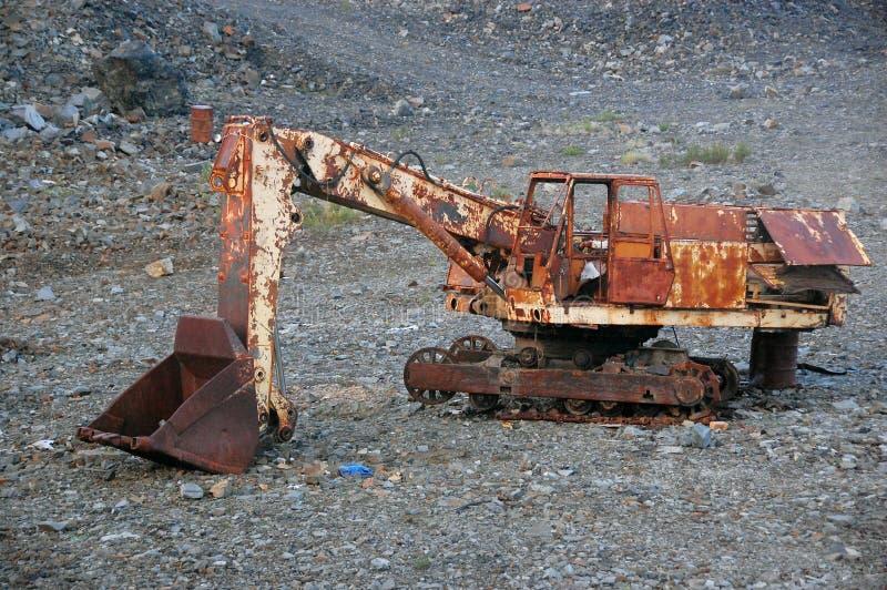 Старый сломанный покинутый ржавый экскаватор на моих стоковая фотография