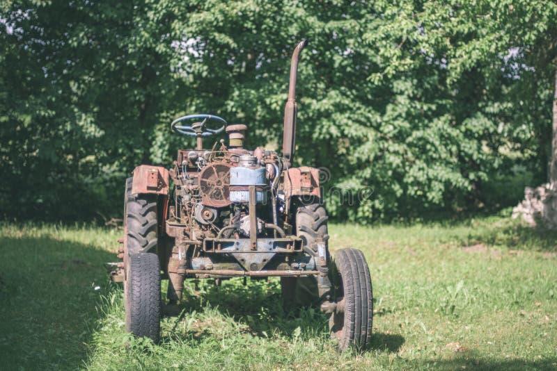 старый трактор с резиновыми автошинами в зеленом дворе сельской местности зеленым летом - винтажным ретро взглядом фильма стоковое изображение
