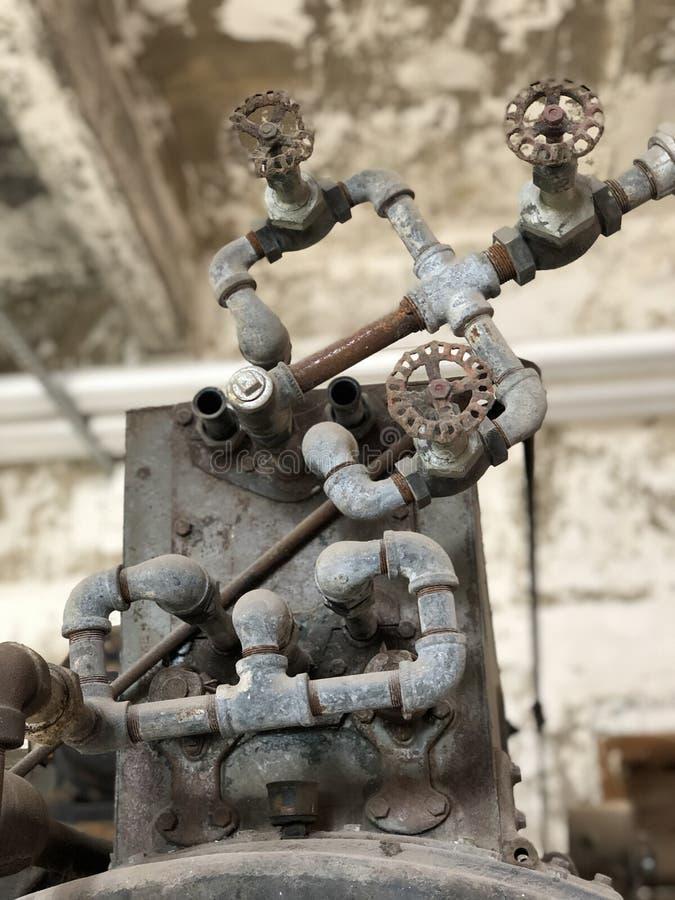 Старый трубопровод в получившемся отказ здании стоковое фото