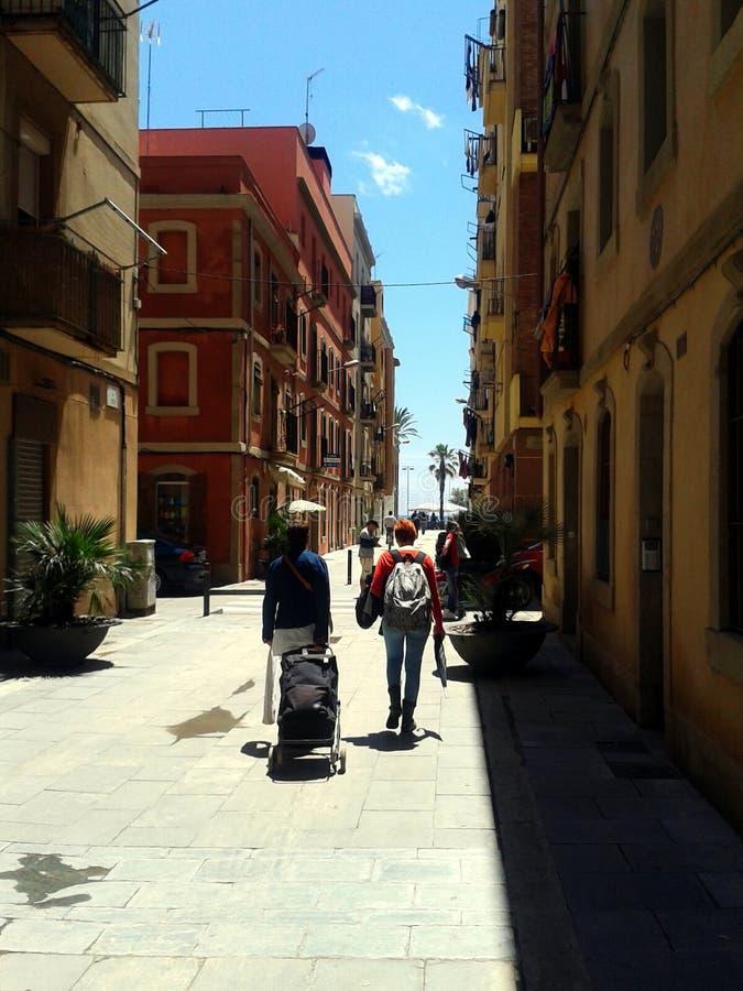 Старый узкий переулок Барселоны водя к морю под голубым небом стоковые фото