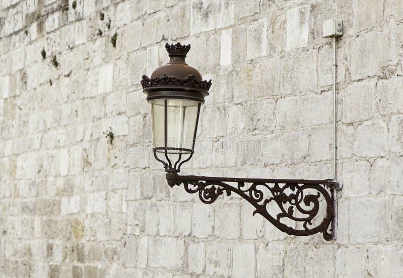 Старый фонарный столб на стене стоковое фото rf