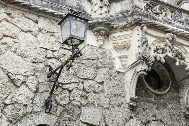 Старый фонарный столб на стене стоковое изображение