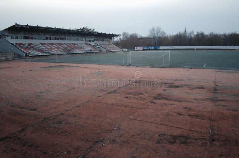 Старый футбольный стадион с искусственной дерновиной Пустая арена с идущим третбаном стоковые фото