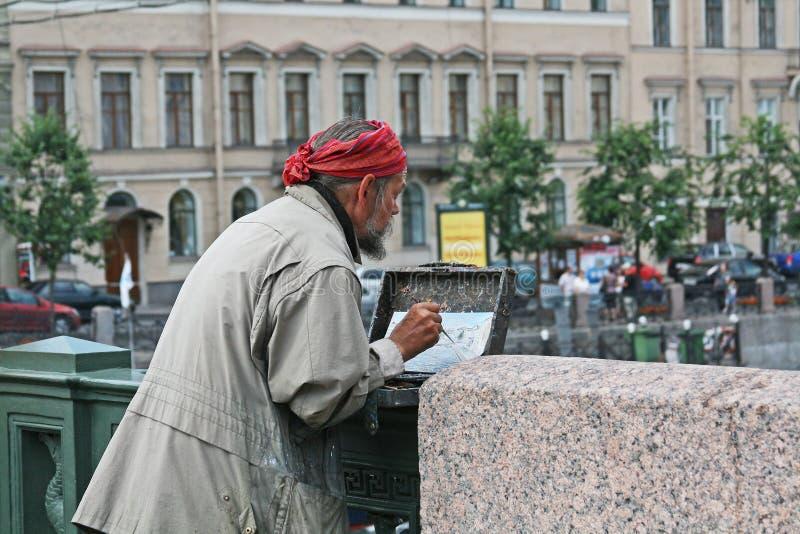Старый художник крася обваловку реки Moika и исторических зданий на мосте в Санкт-Петербурге стоковая фотография rf