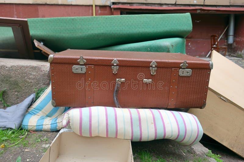 Старый чемодан брошенный в погань стоковое фото