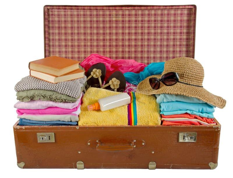 Старый чемодан год сбора винограда упакованный с одеждами стоковое фото rf