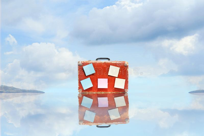 Старый чемодан с пустыми стикерами, с отражением, против голубого неба с красивыми облаками скопируйте космос перемещение карты d стоковые фотографии rf