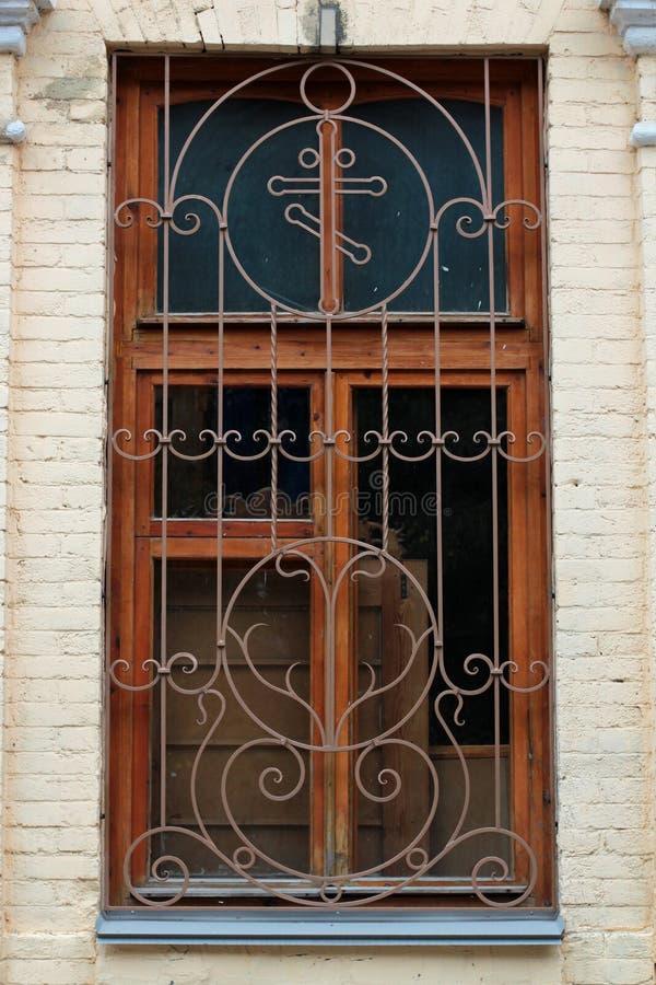 Старый чугунный гриль, декоративный элемент безопасностью Старый гриль на окне старого дома с красивым wa кирпича стоковая фотография
