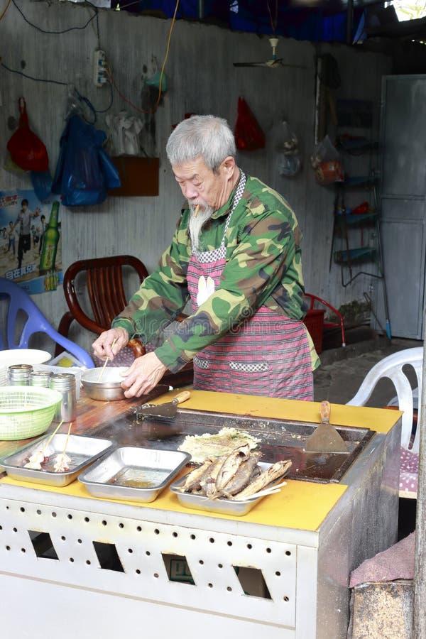 Старый шеф-повар делая закуску стоковое фото