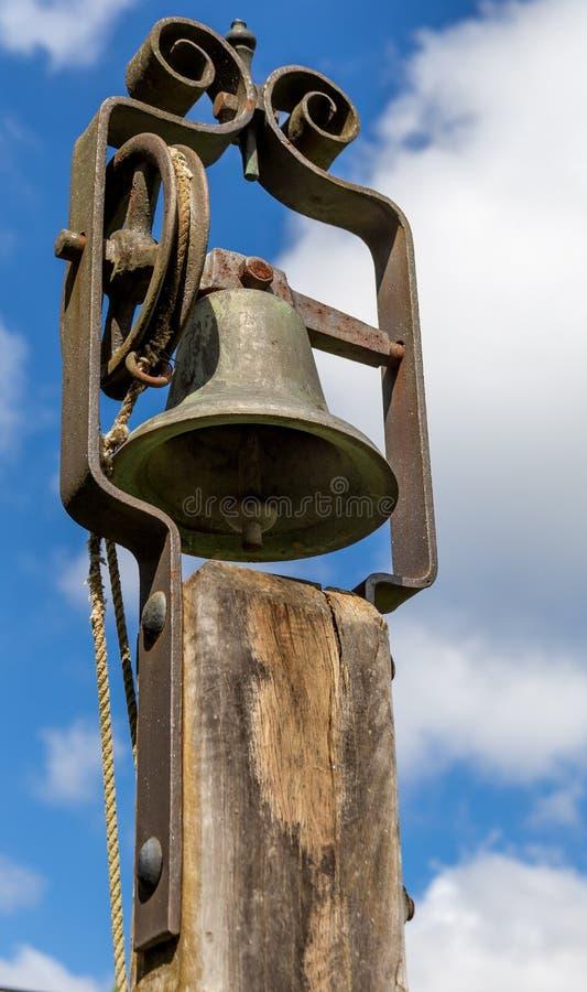 Старый школьный звонок изолированный против неба стоковая фотография rf
