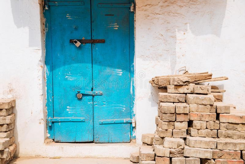 Старый экстерьер дома, голубая дверь и штабелированные кирпичи на Madurai, Индии стоковое изображение