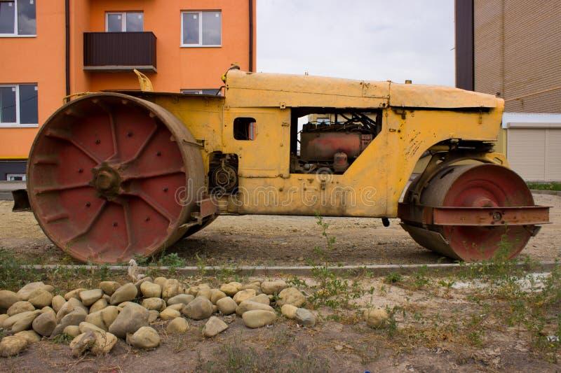 Старый paver на предпосылке дороги и нового дома r стоковая фотография rf